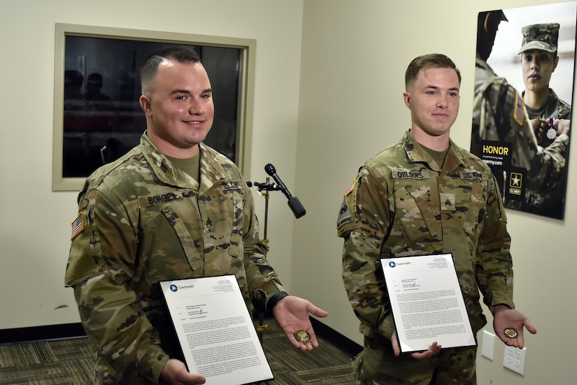 two soldiers presented with certificates.