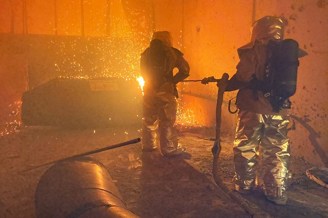 Two soldiers cast a flame at a wall.