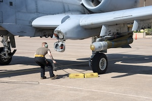 Crew chief pulls the chocks from the wheel of an A-10