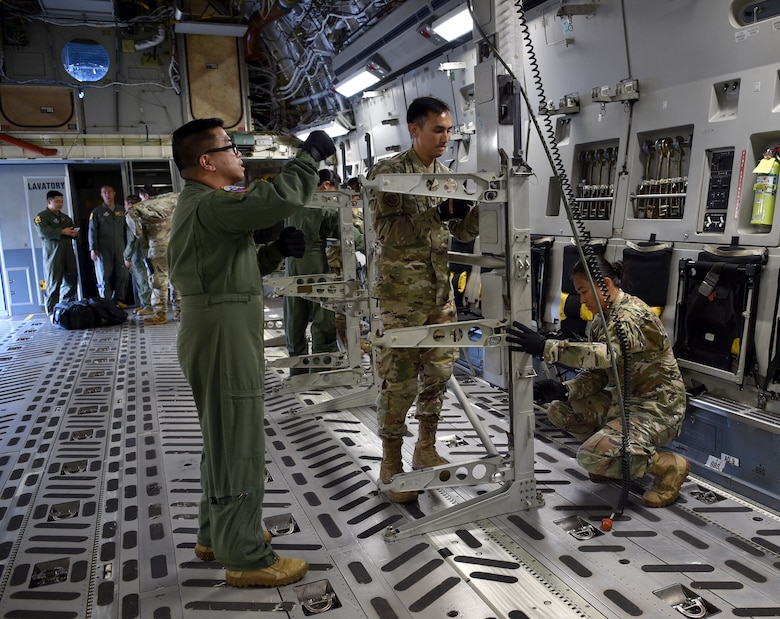 Major Joel Villavert, 613th Air Operations Center, Capt. John Penaranda, 624th Civil Engineer Squadron, and Capt. Louise Sarabosing, 624th Aeromedical Staging Squadron, prepare a C-17 for an aeromedical evacuation demonstration at Joint Base Pearl Harbor-Hickam, Hawaii, May 25, 2021. In honor of Asian American Pacific Islander Heritage Month, active duty, Air Force Reserve, and Air National Guard Airmen of Asian American and Pacific Islander descent came together to demonstrate Air Force capabilities for University of Hawaii ROTC cadets. (U.S. Air Force photo by 1st Lt. Amber R. Kelly-Herard)