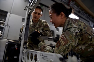 Captain John Penaranda, 624th Civil Engineer Squadron, and Capt. Louise Sarabosing, 624th Aeromedical Staging Squadron, prepare a C-17 for an aeromedical evacuation demonstration at Joint Base Pearl Harbor-Hickam, Hawaii, May 25, 2021. In honor of Asian American Pacific Islander Heritage Month, active duty, Air Force Reserve, and Air National Guard Airmen of Asian American and Pacific Islander descent came together to demonstrate Air Force capabilities for University of Hawaii ROTC cadets. (U.S. Air Force photo by 1st Lt. Amber R. Kelly-Herard)