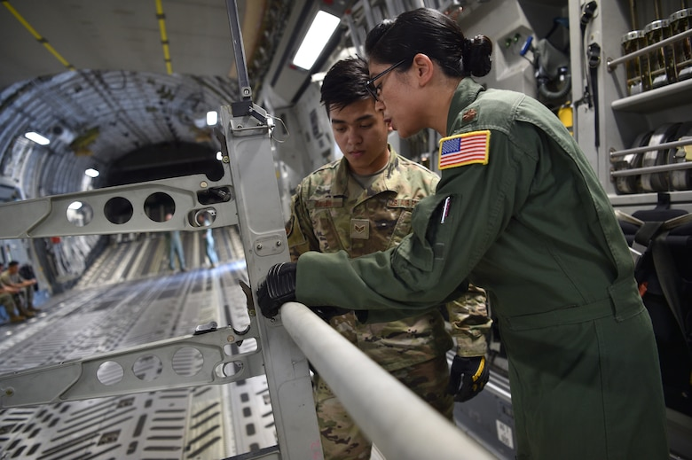 Senior Airman Ramel Baylon, 624th Civil Engineer Squadron, and Maj. Jeanette Williford, 613th Air Operations Center, prepare a C-17 for an aeromedical evacuation demonstration at Joint Base Pearl Harbor-Hickam, Hawaii, May 25, 2021. In honor of Asian American Pacific Islander Heritage Month, active duty, Air Force Reserve, and Air National Guard Airmen of Asian American and Pacific Islander descent came together to demonstrate Air Force capabilities for University of Hawaii ROTC cadets. (U.S. Air Force photo by 1st Lt. Amber R. Kelly-Herard)