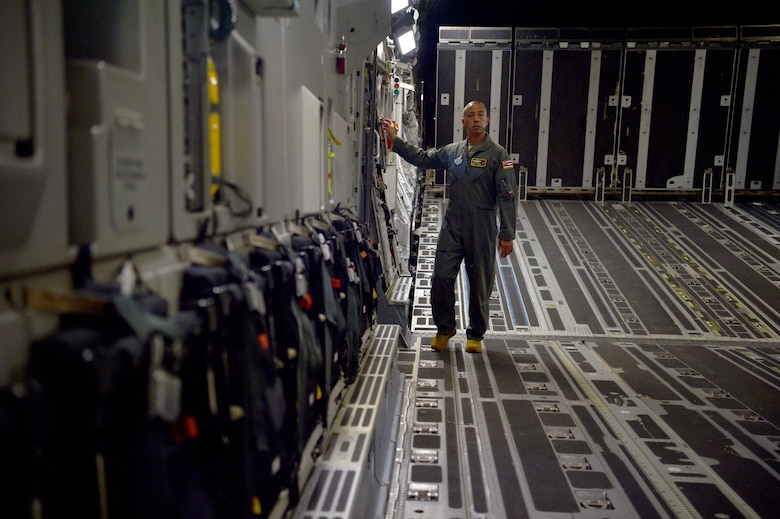 Senior Master Sgt. Brandon Sarceda, 204th Airlift Squadron loadmaster, inspects a C-17 Globemaster before taking off at Joint Base Pearl Harbor-Hickam, Hawaii, May 25, 2021. In honor of Asian American Pacific Islander Heritage Month, the 15th Wing and 154th Wing flew a routine training mission composed with aircrew and maintainers who were all of Asian American or Pacific Islander descent and were a mix of active duty and Air National Guard members. (U.S. Air Force photo by 1st Lt. Amber R. Kelly-Herard)