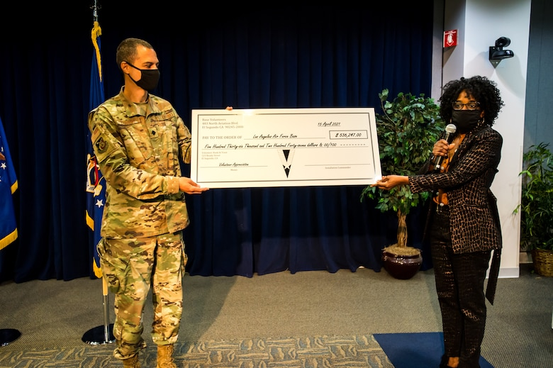 """Lt. Col. John Francis, 61st Air Base Group IMA to the Deputy Commander and Ms. Cathy Howard, Flight Chief, Airman and Family Readiness, present a """"cost savings"""" check for $536,247 to Los Angeles Air Force base which represent the 19,000 volunteer hours those individuals donated to the base during the Los Angeles Air Force Base Volunteer Appreciation Ceremony. (U.S. Space Force photo by Van Ha)"""