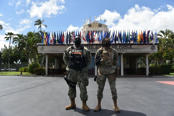 U.S. Navy Master at Arms Petty Officer 2nd Class Samuel A. Poku Jr., and U.S. Air Force Tech. Sgt. Alauna Pruitt, 647th Security Forces Squadron personnel, provide security in front of base operations at Joint Base Pearl Harbor-Hickam, Hawaii, April 29, 2021. The 647th SFS ensures the safety of people, property, and resources on the installation.  (U.S. Air Force photo by Tech. Sgt. Anthony Nelson Jr. )