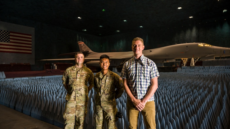 PFS 6.42 project test lead engineer, Capt. Shawn Whitney, BAF project engineer, 1st Lt. Kevin Lasquete, and BAF Project Manager, Justin Duhart, pose for a photo in front of a B-1B Lancer inside the Benefield Anechoic Facility at Edwards Air Force Base, California, May 20. The Lancer, from the 337th Test and Evaluation Squadron, 53rd Wing, out of Dyess Air Force Base, Texas, will be used to conduct testing of PFS 6.42. (Air Force photo by Giancarlo Casem)