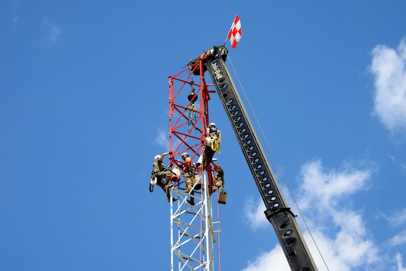 An image of Airmen with the Massachusetts and Pennsylvania Air National Guard connecting the top section of a radio communications tower being hoisted by mobile crane.
