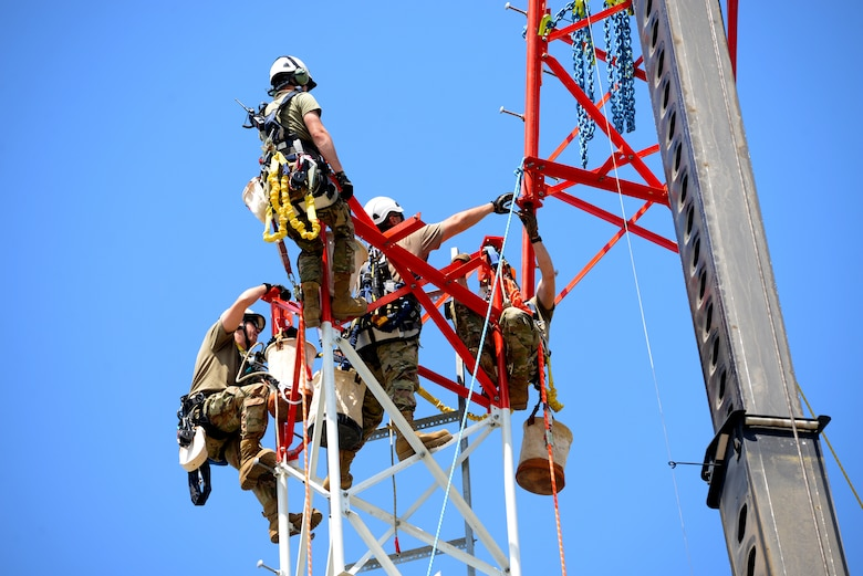 An image of Airmen connecting the final section of a radio communications tower.