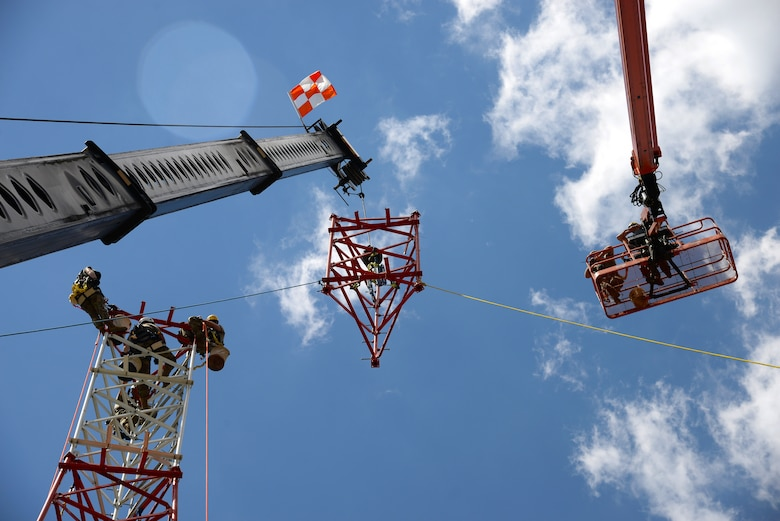 An image of Airmen with the Massachusetts and Pennsylvania Air National Guard working in unison as they use climbing gear to secure themselves safely to a tower, operate a high lift for inspection purposes and use a mobile crane to hoist and connect the top section of a radio communications tower.