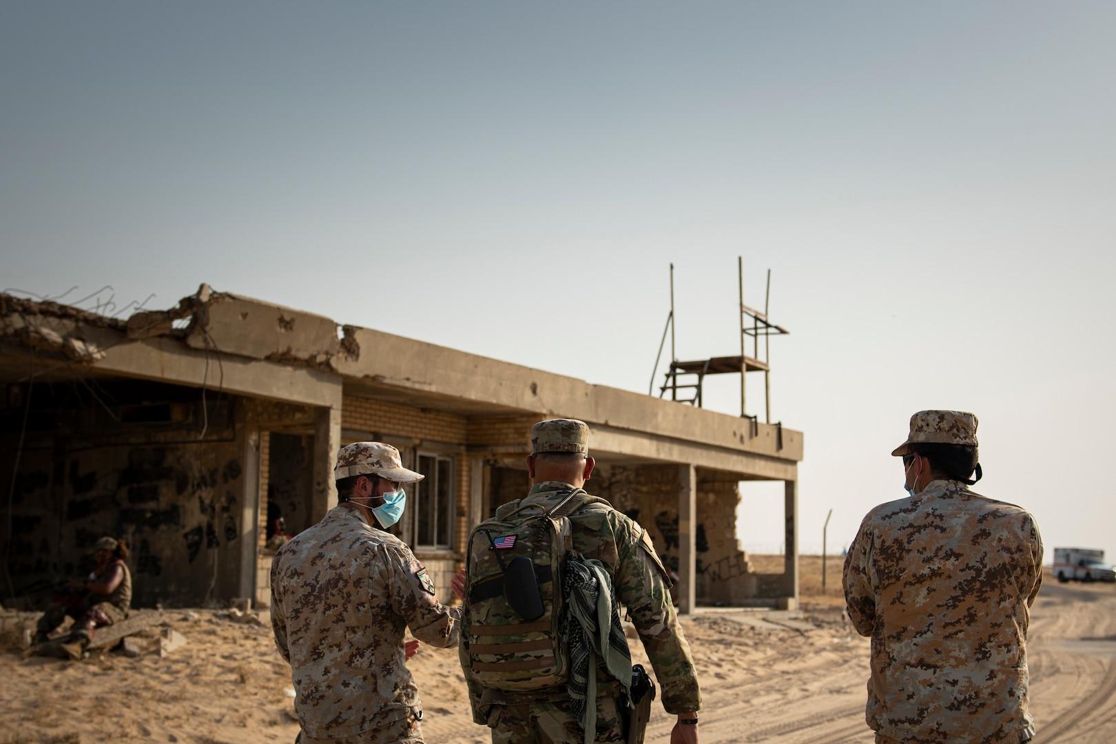 People walk along the desert next to deserting buildings.