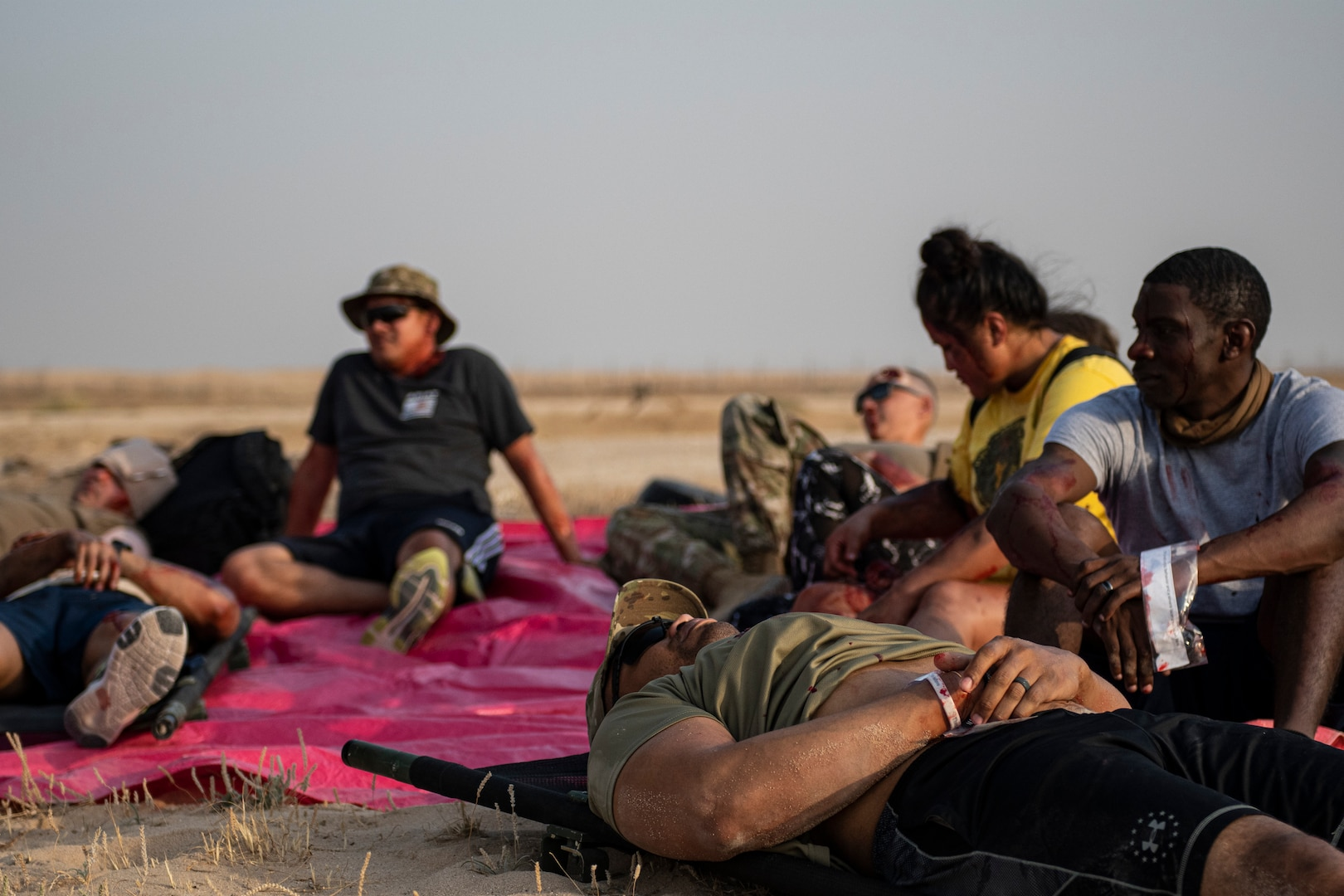 Volunteers acting as casualties with simulated injuries gather in the desert.