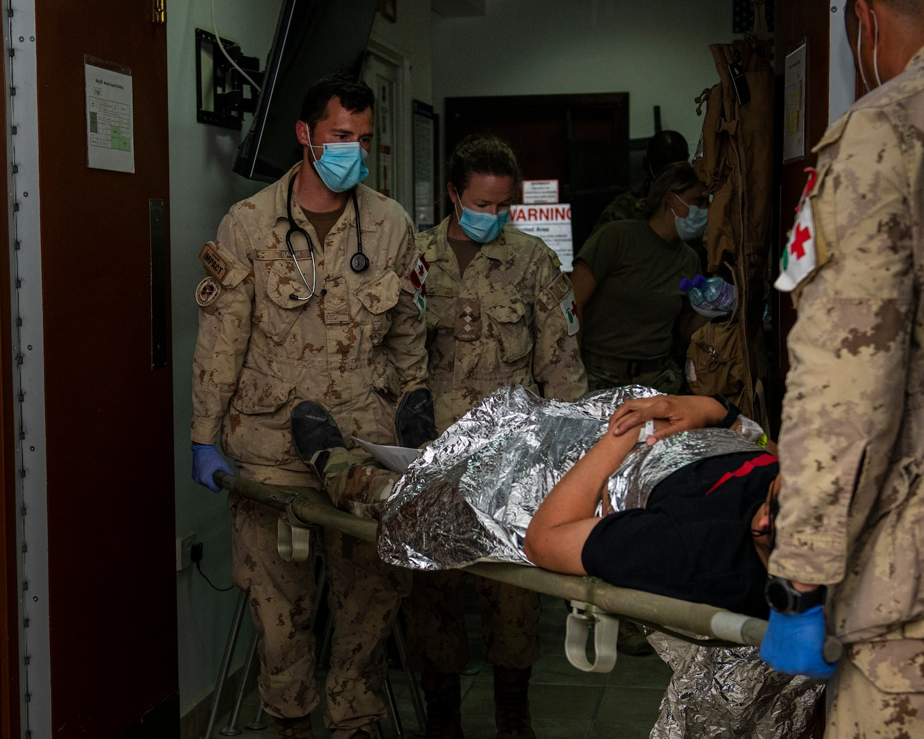 Medical personnel carry a stretcher into a room.