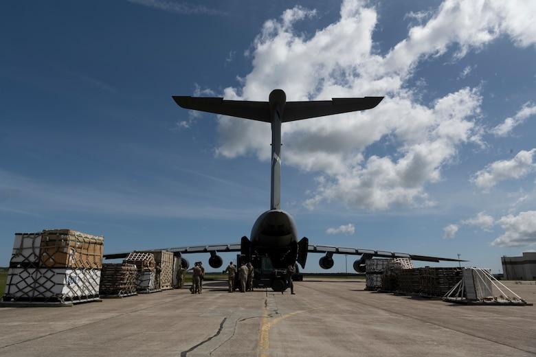 Airmen and cargo surrounding a plane