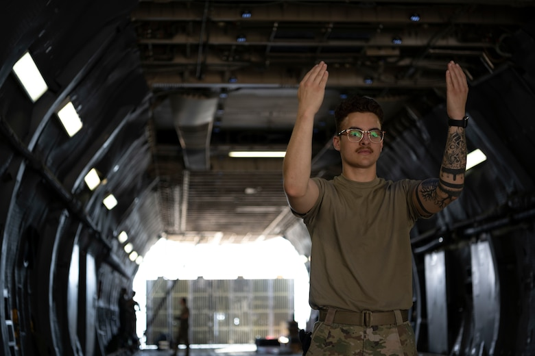 Airman with hands arms up marshalling