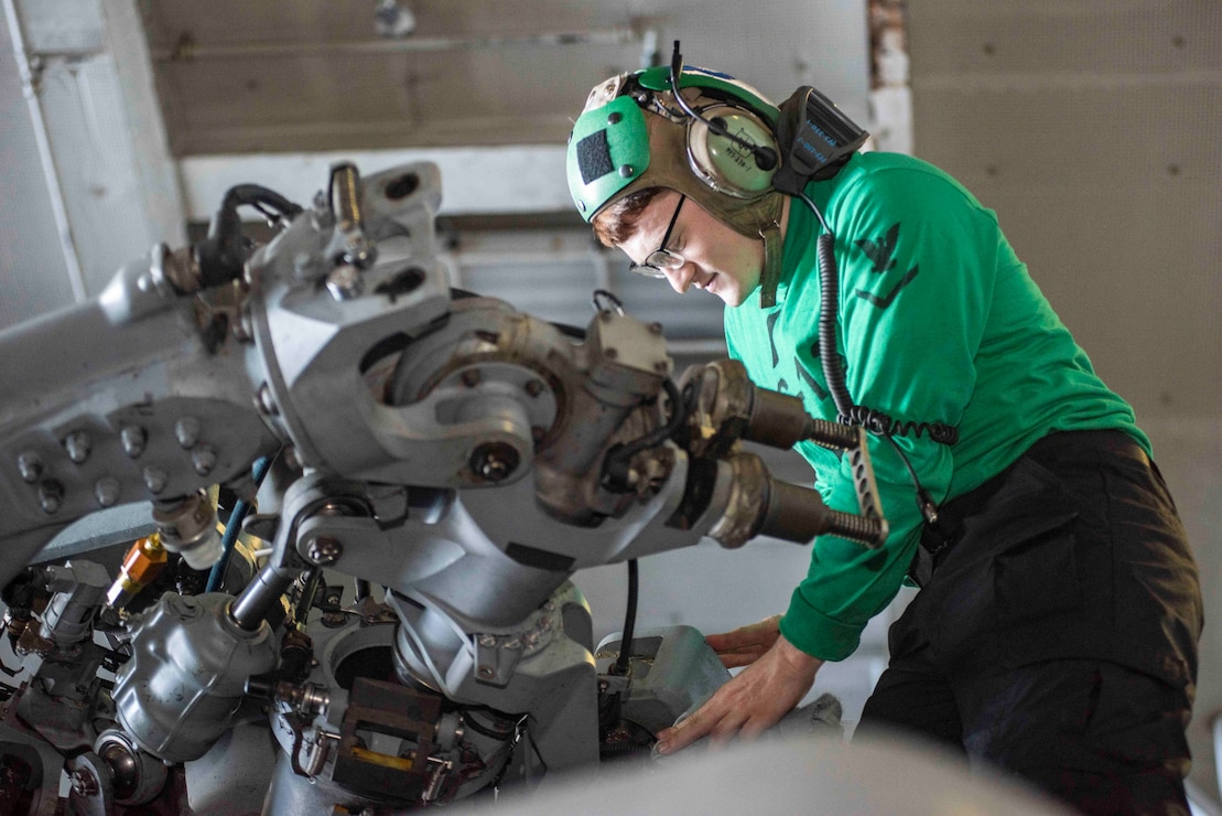 viation Electrician's Mate 3rd Class Brenden Eaves, from Earlville, New York, conducts maintenance on an MH-60S Sea Hawk attached to the Golden Falcons of Helicopter Sea Combat Squadron (HSC) 12, in the hangar bay of the U.S. Navy's only forward-deployed aircraft carrier USS Ronald Reagan (CVN 76).