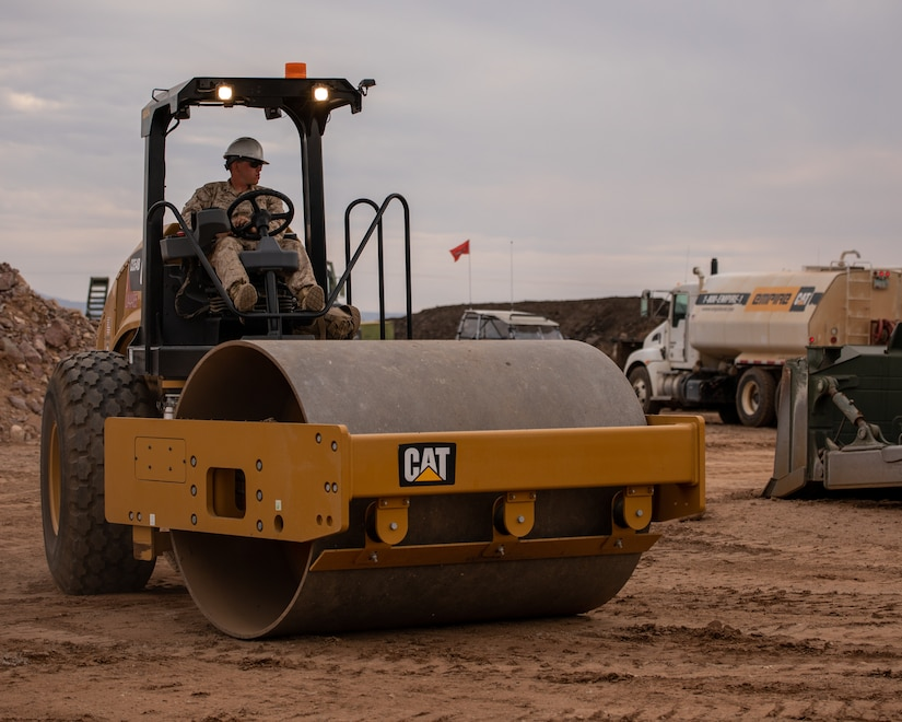 A Marine drives a piece of construction equipment over a dirt area.