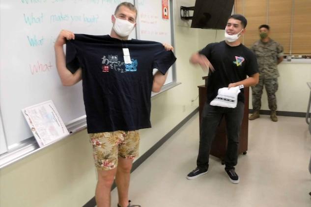 基地内で開催されている地域住民のための社会人英語講座で、受講者たちから贈られた沖縄のTシャツを広げるブライアン・ゴフ中尉、2021年5月26日、米海兵隊基地キャンプ・シュワブ教育センター