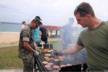 部隊の隊員や英会話クラスの受講生など、100人近くを招いて、自前でBBQを開催し、パティをBBQで焼くブライアン・ゴフ中尉、2021年3月24日、米海兵隊基地キャンプ・シュワブ