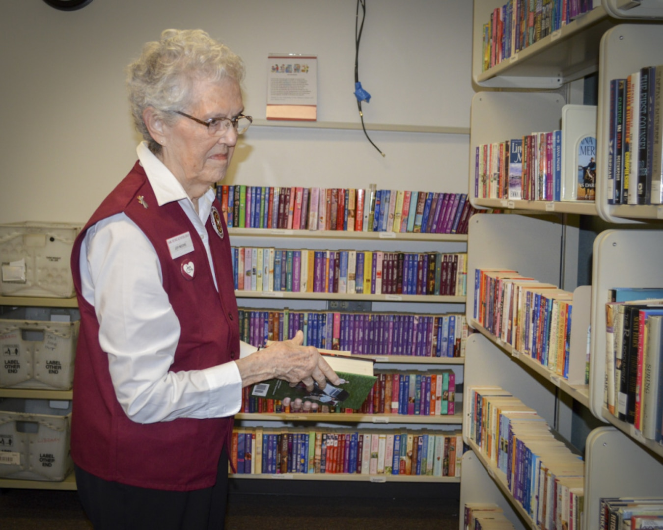 Joy Moore, volunteer, sorts books in the Patient Library at Brooke Army Medical Center.
