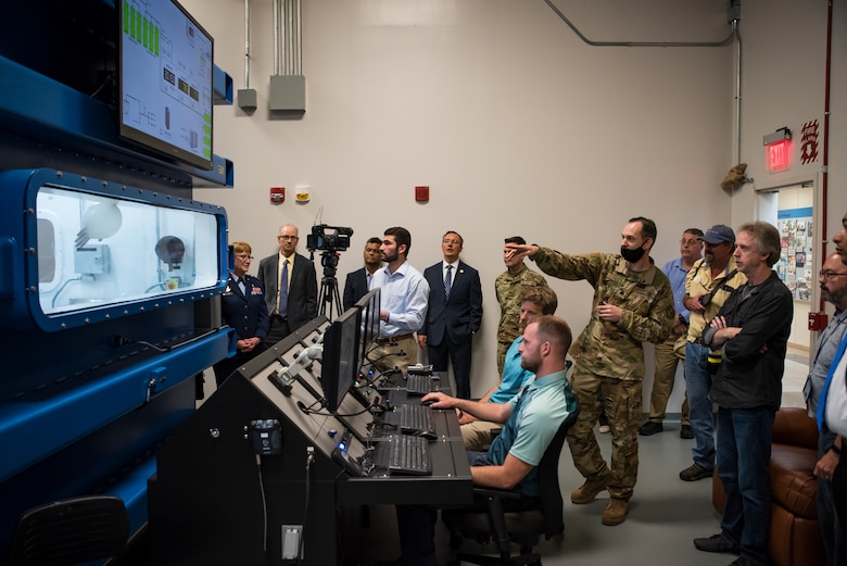 Lt. Col. Nathan Maertens, aerospace physiology division chief in the 711th Human Performance Wing, describes a decompression demonstration in research altitude chamber one following a ribbon-cutting ceremony May 27 hosted by the Air Force Research Laboratory's 711 HPW. (U.S. Air Force photo by Richard Eldridge)