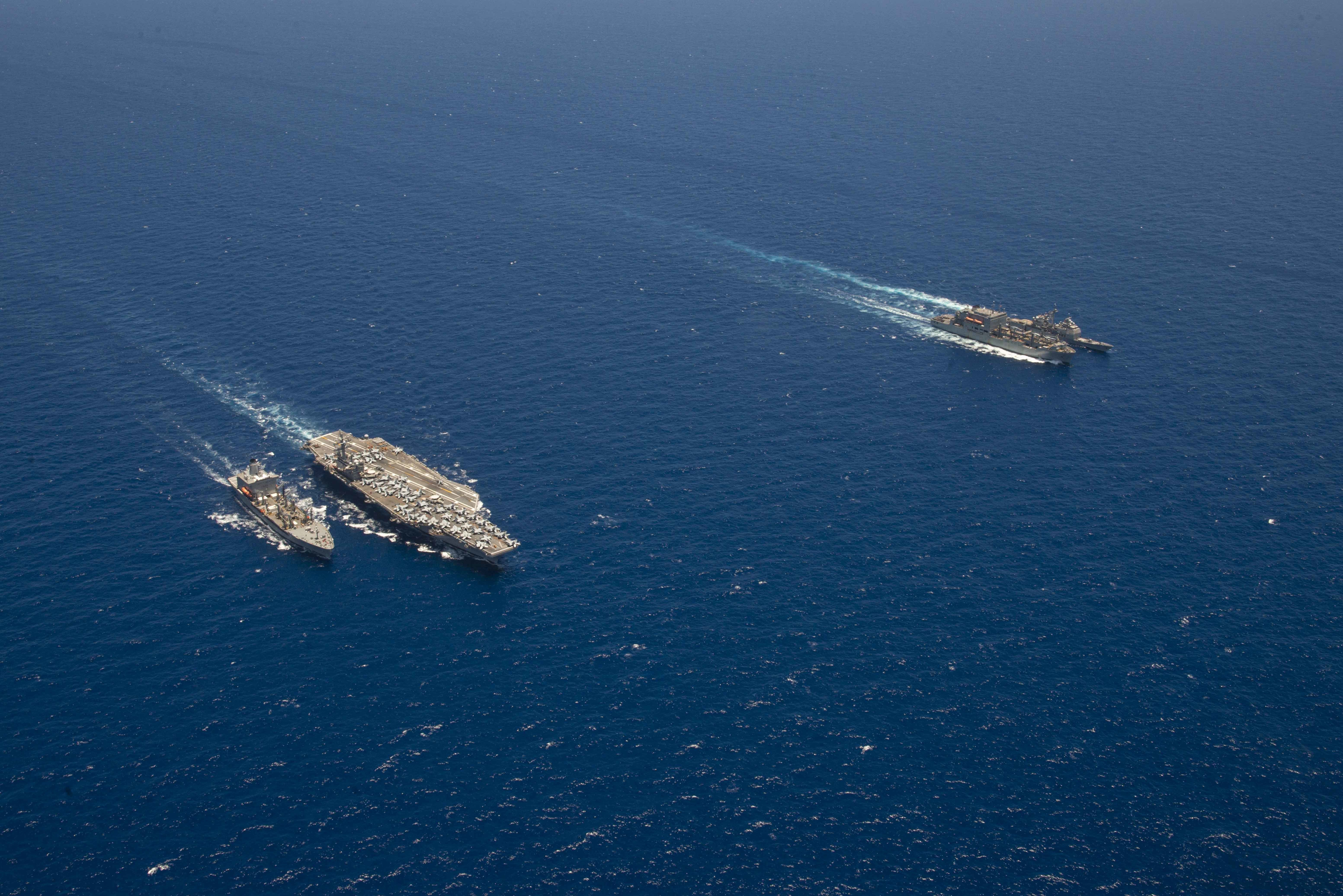USS Ronald Reagan (CVN 76), conducts a fueling-at-sea with the fleet replenishment oiler USNS Pecos (T-AO 195), while USS Shiloh (CG 67) conducts a USNS Charles Drew (T-AKE 10).