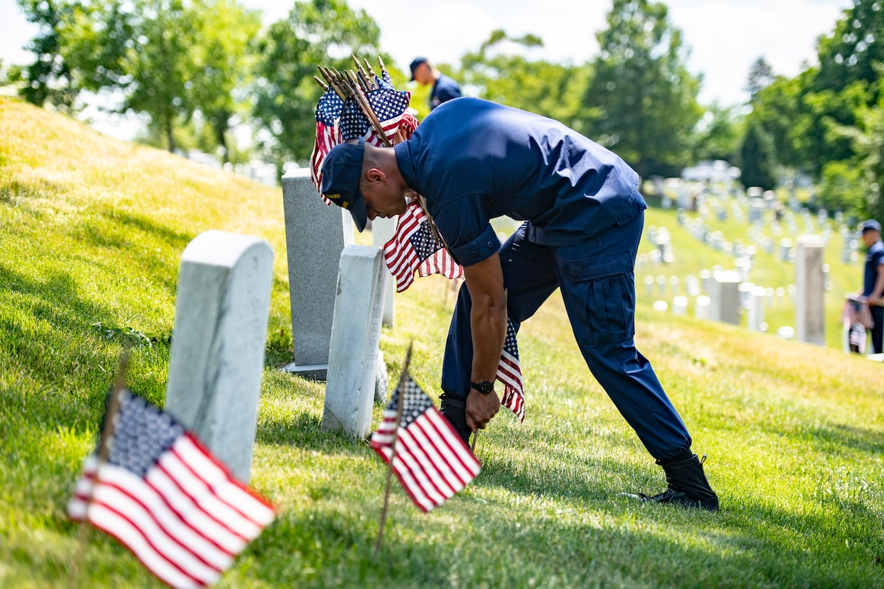 Service members place flags on headstones.