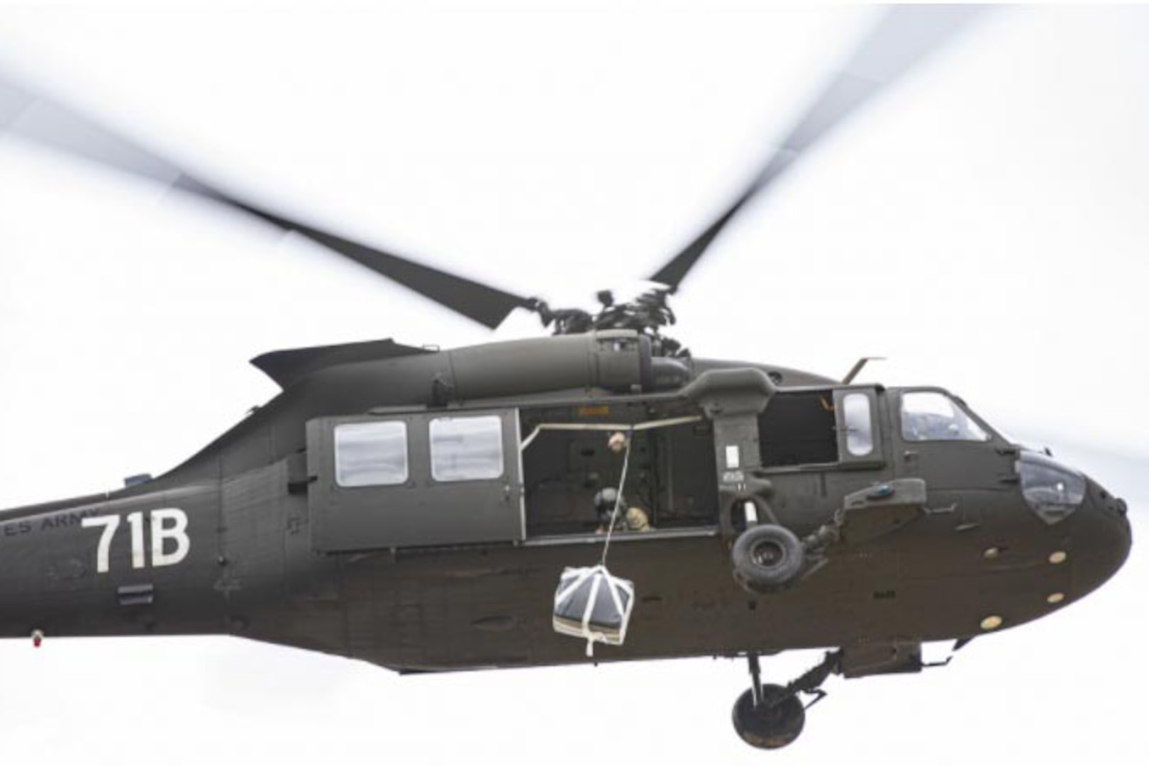 A helicopter flies while a crew member inside the helicopter prepares an emergency re-supply drop.