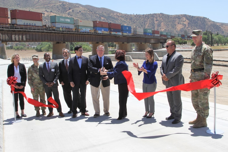 Representatives of local, county, state and federal agencies gather near the Santa Ana River in Corona, California, May 27, 2021, to mark the official completion of the BSNF Railroad Bridge Pier Protection Project in Corona, California. The purpose of the project is to minimize risk to the bridge in flood conditions and during increased water releases from Prado Dam resulting from periods of heavy rainfall.