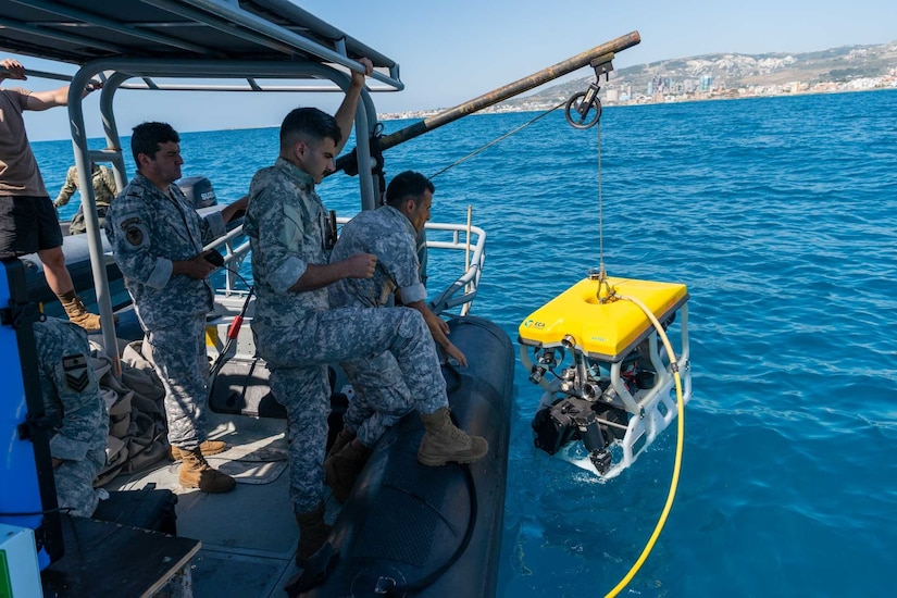 Several uniformed personnel stand at the edge of a small watercraft and operate a crane, which is being used to remove a small submersible vehicle from the water.