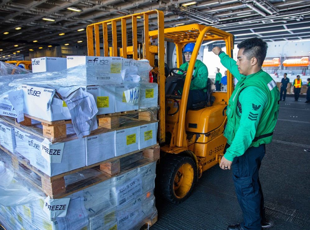 Logistics Specialist 1st Class Aaron Azuma, from Olongapo, Philippines, directs a cargo onload aboard the U.S. Navy's only forward-deployed aircraft carrier, USS Ronald Reagan (CVN 76).