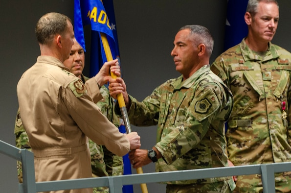 U.S. Air Force Lt. Gen. Greg Guillot, 9th Air Force (Air Forces Central) commander, left, passes the unit guidon to Col. Joshua Koslov, 609th Air Operations Center commander, during the 609th AOC change of command ceremony Al Udeid Air Base, Qatar, May 27, 2021. The Airmen of the 609th AOC work alongside joint and international partners from 18 nations to plan, produce, and execute the daily Air Tasking Order on behalf of Guillot, who also serves as the Combined Forces Air Component Commander. (U.S. Air Force photo by Tech. Sgt. Dylan Nuckolls)