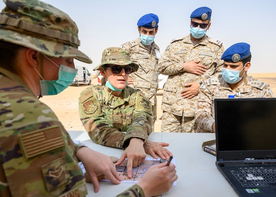 Senior Airman Magdalena Polak, 378th Air Expeditionary Wing Host Nation Coordination Cell translator, relays the planned actions for a chemical, biological, radiological and nuclear response exercise to members of the Royal Saudi Air Force, Prince Sultan Air Base, Kingdom of Saudi Arabia, May 26, 2021. The combined exercise demonstrates the emergency management integration between USAF and RSAF CBRN response units while also familiarizing each unit with the other's techniques and procedures. (U.S. Air Force photo by Senior Airman Samuel Earick)