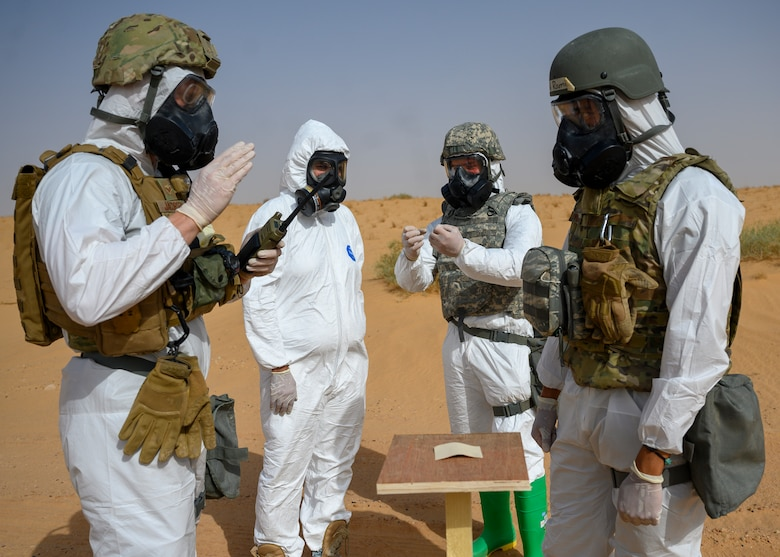 Members of the 378th Civil Engineer Squadron emergency management flight and members of the Royal Saudi Air Force discuss simulated readings on an M9 paper during a chemical, biological, radiological and nuclear response exercise, Prince Sultan Air Base, Kingdom of Saudi Arabia, May 26, 2021. The combined exercise demonstrates the emergency management integration between USAF and RSAF CBRN response units while also familiarizing each unit with the other's techniques and procedures. (U.S. Air Force photo by Senior Airman Samuel Earick)