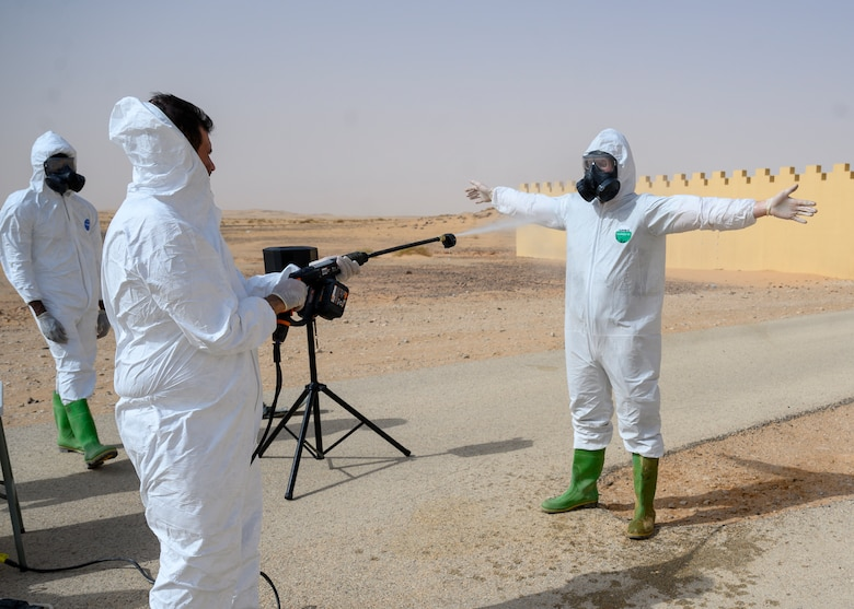 Members of the Royal Saudi Air Force spray members of the 378th Civil Engineer Squadron emergency management flight to practice decontaminating techniques after a chemical, biological, radiological and nuclear response exercise, Prince Sultan Air Base, Kingdom of Saudi Arabia, May 26, 2021. The combined exercise demonstrates the emergency management integration between USAF and RSAF CBRN response units while also familiarizing each unit with the other's techniques and procedures. (U.S. Air Force photo by Senior Airman Samuel Earick)