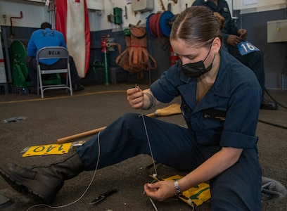 Seaman Kayla Raffaele, from New Rochelle, New York, splices a pennant to a phone-and-distance line in the hangar bay of the Nimitz-class aircraft carrier USS Harry S. Truman (CVN 75) during sea trials after completing an extended carrier incremental availability.