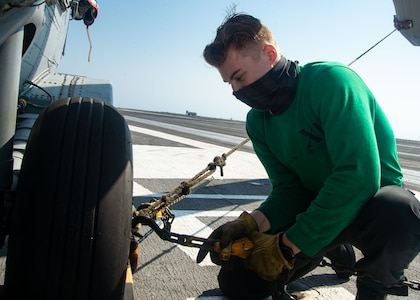 """Airman Shane Gilson, from Paulden, Arizona, chocks an MH-60S Seahawk, attached to the """"Dragon Slayers"""" of Helicopter Sea Combat Squadron (HSC) 11, to the flight deck of the Nimitz-class aircraft carrier USS Harry S. Truman (CVN 75) during sea trials after completing an extended incremental availability."""