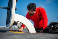 Aviation Boatswain's Mate (Handling) 3rd Class Joseph Vasquez, from Houston, cleans a hatch on the flight deck of the Nimitz-class aircraft carrier USS Harry S. Truman (CVN 75) during sea trials after completing an extended carrier incremental availability.