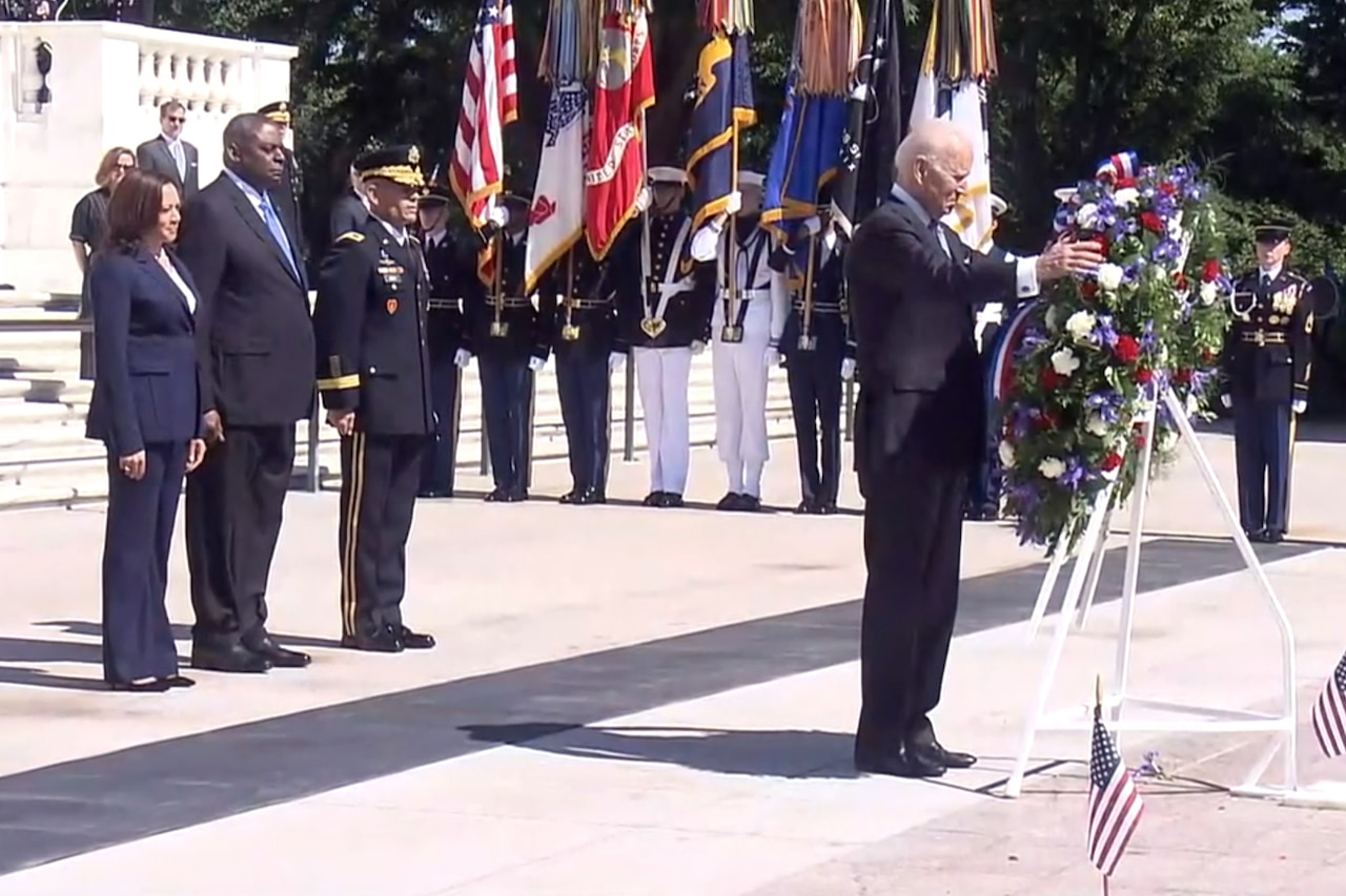 A man places his hand on a wreath, which is hanging on a metal stand.  Behind him, three people stand side-by-side with their hands at their side.