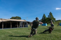 Airmen pulling strings attached to a cover to position tent covering over metal beams.