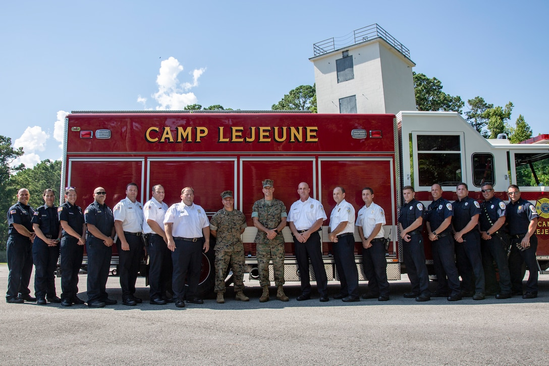 U.S. Marine Corps Brig. Gen. Andrew M. Niebel, center right, commanding general, Marine Corps Installations East-Marine Corps Base Camp Lejeune and Col. Kyle G. Phillips, center left, commanding officer, Headquarters and Support Battalion, Marine Corps Installations East-Marine Corps Base Camp Lejeune stand with the Camp Lejeune Fire and Emergency Services Division, at their Training Ground, on MCB Camp Lejeune, North Carolina, July 9, 2021. Niebel and Phillips visited Camp Lejeune Fire and Emergency Services to survey their capabilities, equipment, and how they operate. (U.S. Marine Corps photo by Lance Cpl. Isaiah Gomez)