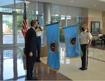 Dr. Brian Lein, Defense Health Agency assistant director, and Col. Daniel Moore, Central Texas Market Director and Commander Carl R. Darnall Army Medical Center unfurl the flags during the DHA's formal establishment ceremony of the Central Texas Market, at the markets main health facility the Carl R. Darnall Army Medical Center 29 Sept.