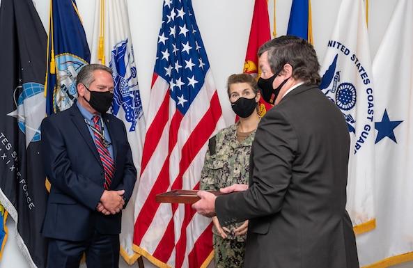 Eddy Poprock, left; Rear Admiral Kristen Fabry, center; Dan Bell, right.