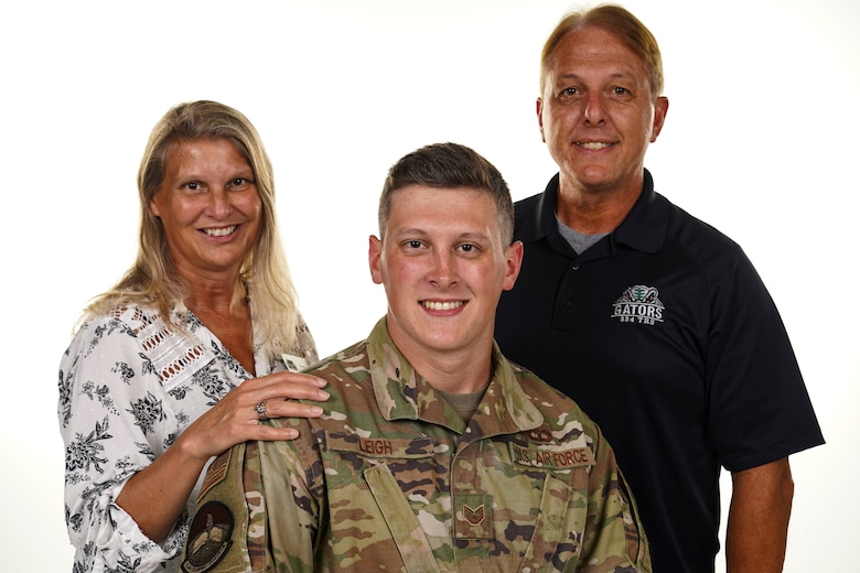 Wynell Leigh, 334th Training Squadron flight secretary, SSgt Justin Leigh, 334th TRS air traffic control instructor and Stanley Leigh, 334th TRS ATC master instructor, pose for a photo inside of Wall Studio at Keesler Air Force Base, Mississippi, Sept. 16, 2021. The Leigh family train Airmen from the 334th TRS side-by-side. (U.S. Air Force photo by Senior Airman Spencer Tobler)