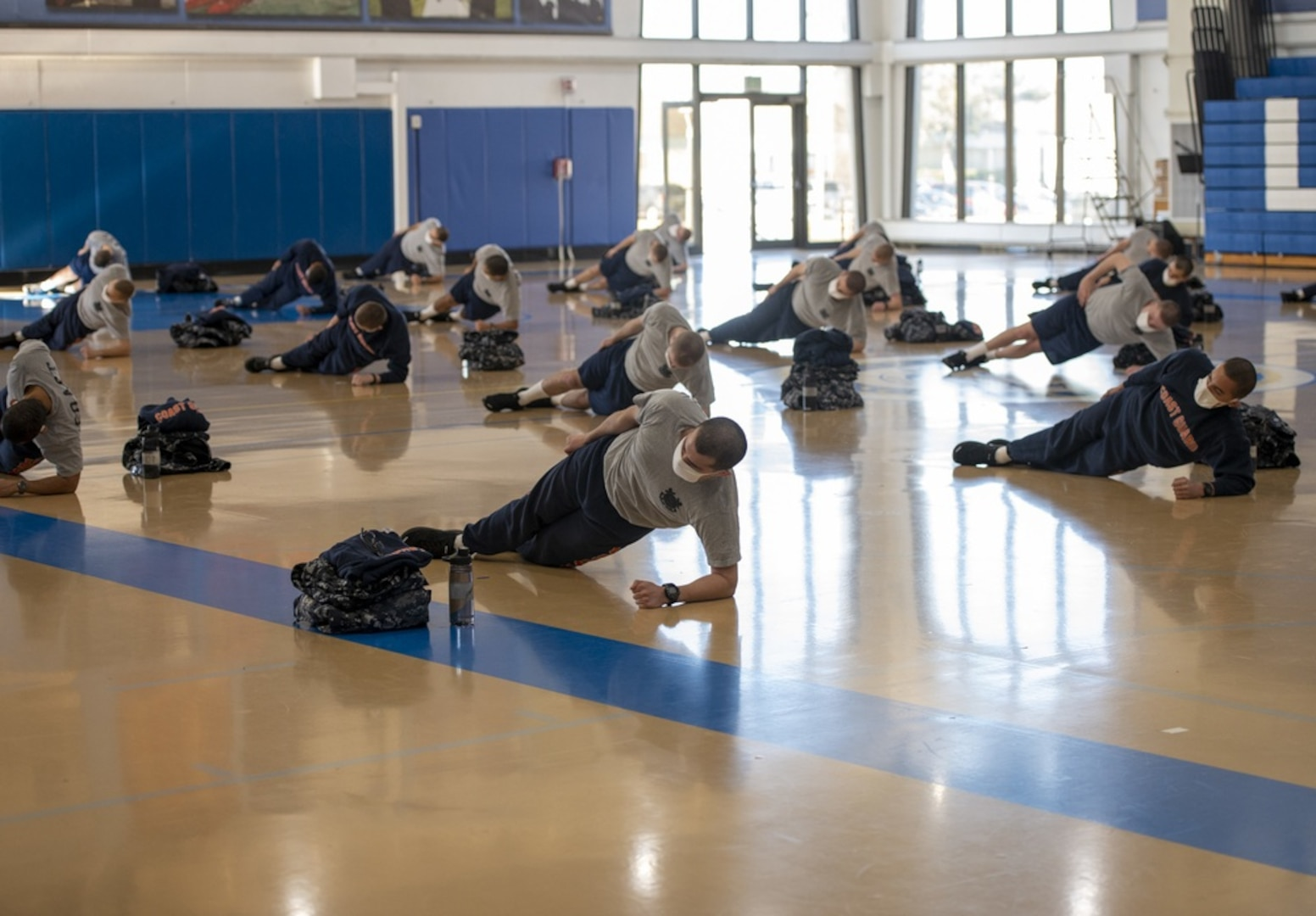 Recruits from company Sierra-199 participate in physical fitness as part of their modified training schedule in the gym at U.S. Coast Guard Training Center Cape May, N.J., Jan. 7, 2021. Training Center Cape May's mission is to deliver dynamic training that sets the foundation for the Coast Guard's professional culture and develops job-ready skills in our recruits to build our workforce for generations to come. (U.S. Coast Guard photo by Seaman Josalyn Brown)