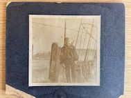 A gangway board aboard an unidentified Revenue Cutter along with an enlisted crewman and pet.