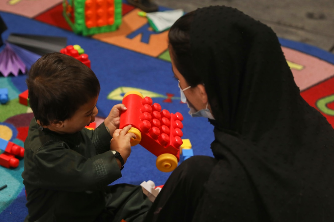 A woman watches as a young child plays with a toy car.