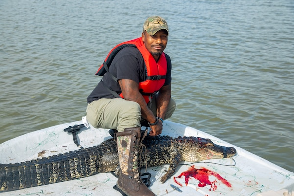 WALLISVILE LAKE, Texas (Sept. 29, 2021) – Reese Green, a combat injured veteran, poses with the 6-foot-plus alligator he hunted at the U.S. Army Corps of Engineers' (USACE) Wallisville Lake Project during the Lonestar Warriors Outdoors Gator Hunt. The event is a sponsored alligator hunt for combat injured veterans. In partnership with the Texas Parks and Wildlife Department game wardens and Lone Star Warriors Outdoors, USACE Galveston hosted the hunt as a way to successfully manage alligator populations in support of environmental stewardship and maintain its wounded warrior outreach program.
