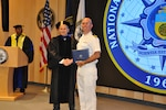 LCDR Alex Homme receives award while earning his master's degree.