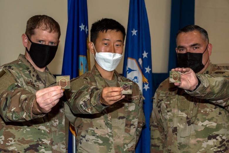 Three men in Air Force uniforms display their rank insignias.