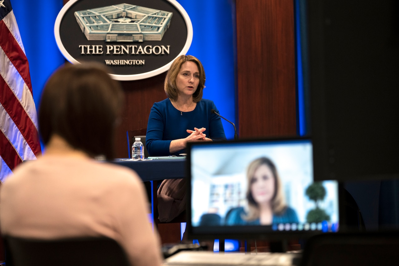 A woman participates in a virtual conversation. The sign behind her indicates that she is speaking from the Pentagon.